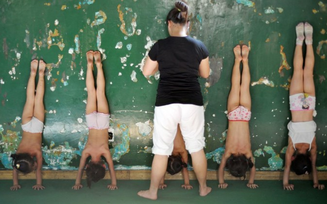 Little girls are practicing handstand, holding their body with their ...